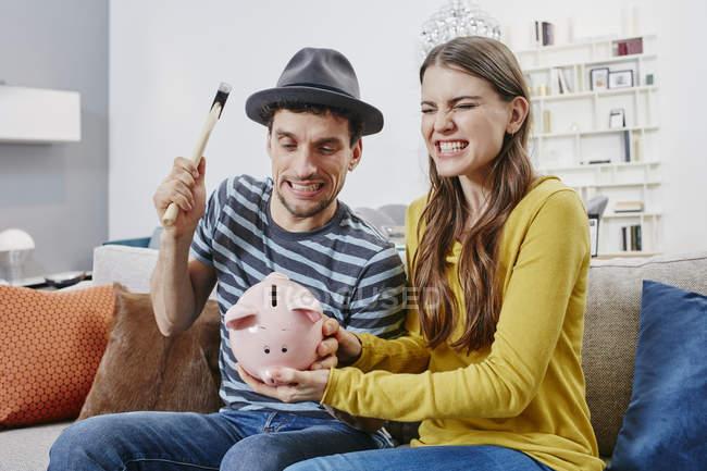 Porträt von paar brechen Sparschwein auf sofa — Stockfoto
