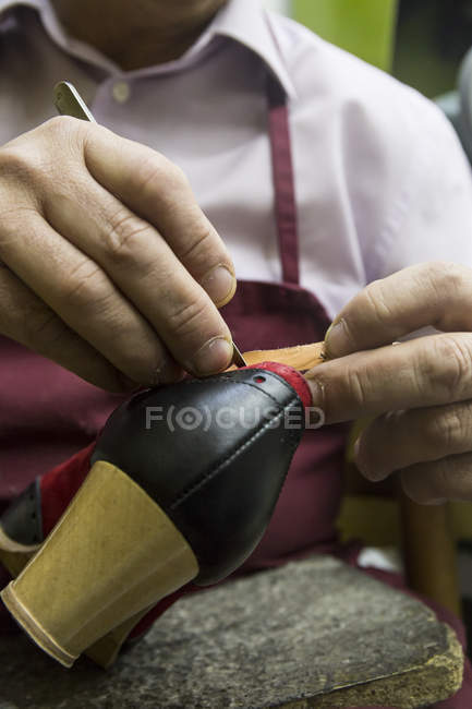 Shoemaker using a knife during a shoemaking in his workshop — Stock Photo