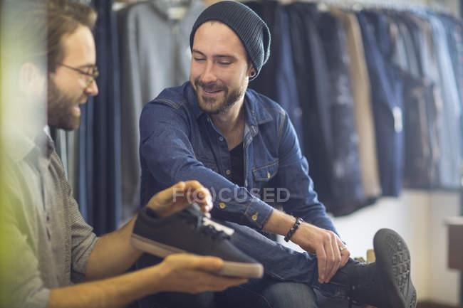 Jeune homme barbu shopping pour chaussures en magasin — Photo de stock