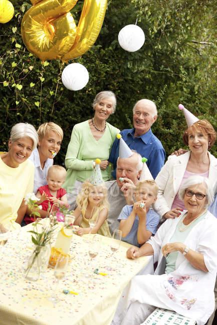 Расширенная семья и друзья празднуют день рождения в саду — стоковое фото