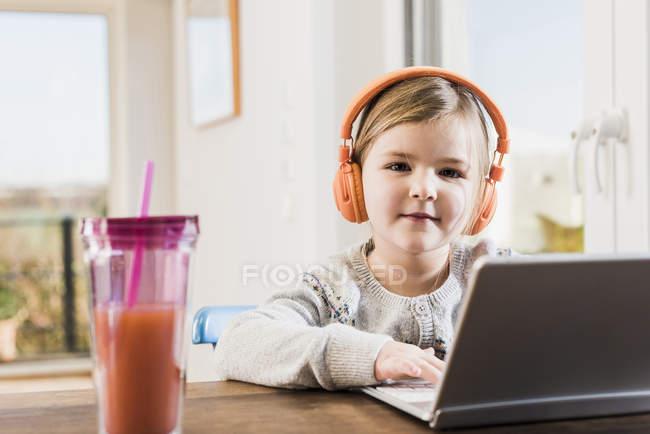 Menina sentada em casa usando laptop e fones de ouvido na mesa — Fotografia de Stock