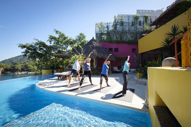 Yoga en grupo haciendo ejercicio en villa frente al mar - foto de stock
