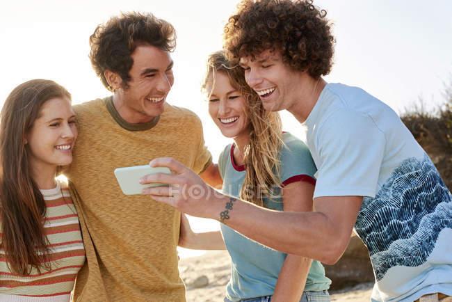 Amigos felizes com telefone celular na praia — Fotografia de Stock