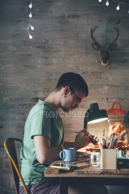 Young man painting animal figurine with paint — Stock Photo