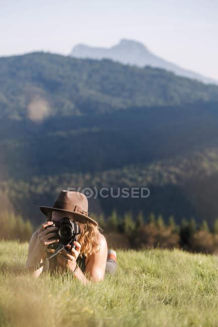 Österreich, mondsee, mondseeberg, junger mann liegt in wiese und macht ein foto — Stockfoto