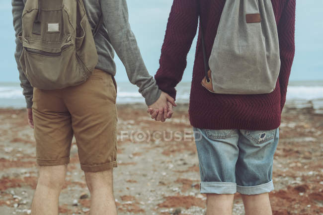 Gay couple holding hands on the beach — Stock Photo