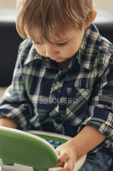 Portrait de garçon en utilisant un ordinateur portable jouet — Photo de stock
