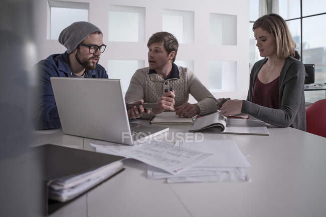 Coworkers having an informal meeting in office with laptop,files and notepads — Stock Photo
