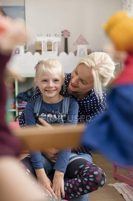 Happy little girl watching Punch and Judy show together with her mother in children's room — Stock Photo