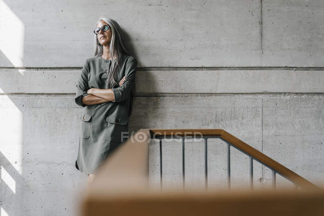 Woman with long grey hair leaning against concrete wall — Stock Photo