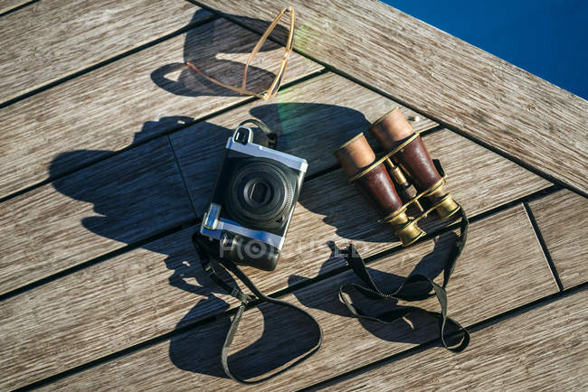 Binoculars, camera and sunglasses on wooden pier — Stock Photo