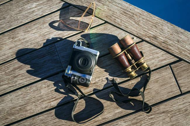 Binóculos, câmera e óculos de sol no cais de madeira — Fotografia de Stock