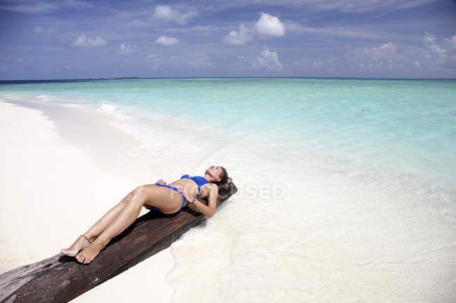 Maldive, donna che prende il sole su un tronco su una spiaggia — Foto stock