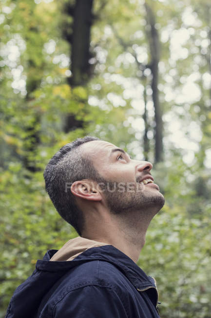 Smiling man standing in the woods and looking up — Stock Photo