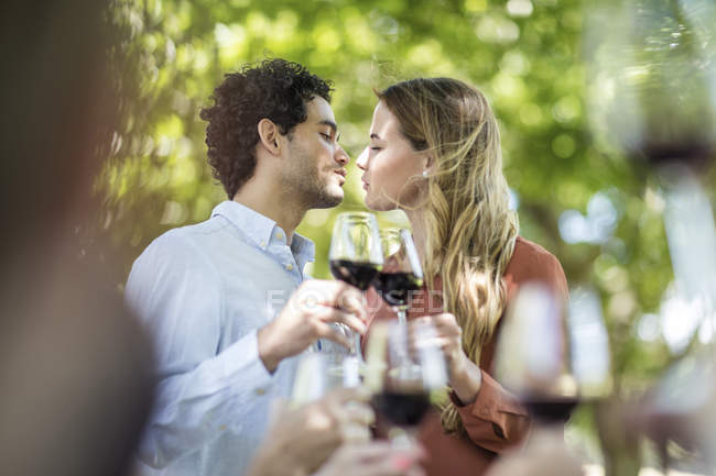 Couple baisant ensemble lever un toast avec des verres de vin à l'extérieur de jardin — Photo de stock