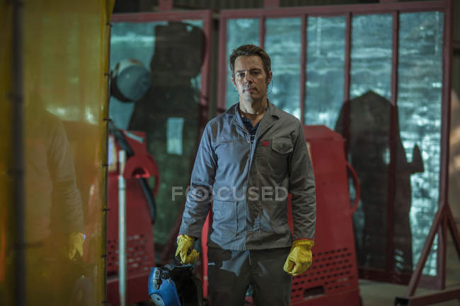 Portrait of confident man holding a welding mask in a factory — Stock Photo
