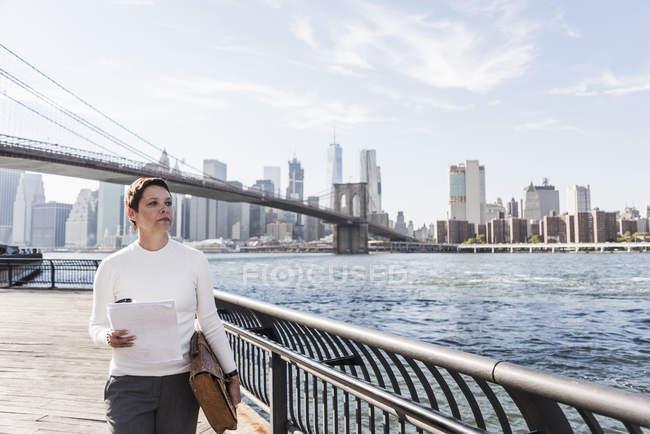 Donna d'affari con documenti davanti allo skyline di Manhattan, Brooklyn, USA — Foto stock