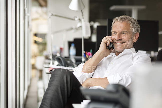 Businessman on cell phone in office — Stock Photo