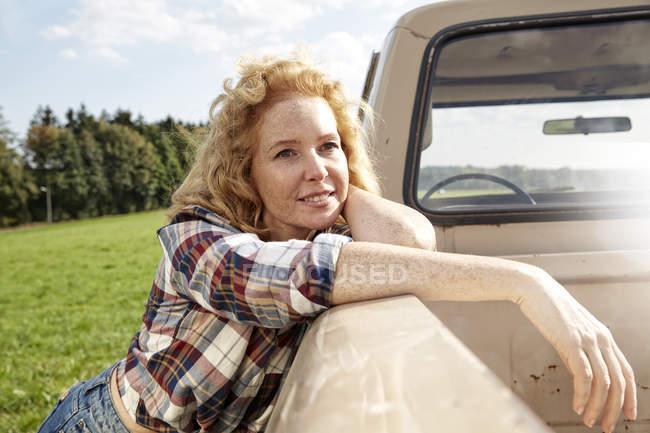Retrato de mujer rubia apoyándose van en la naturaleza - foto de stock