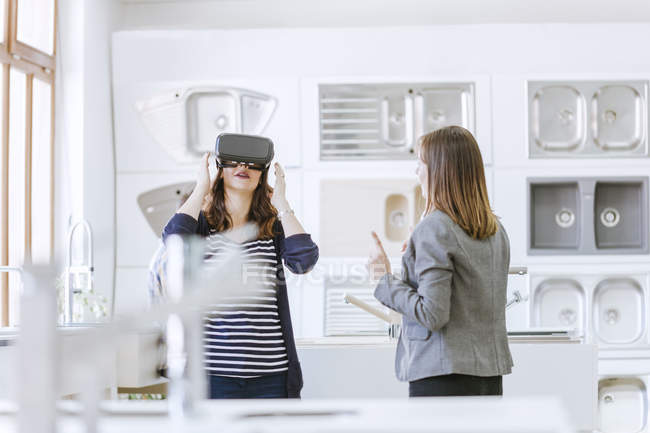 Woman in virtual reality glasses in plumbing shop — Stock Photo