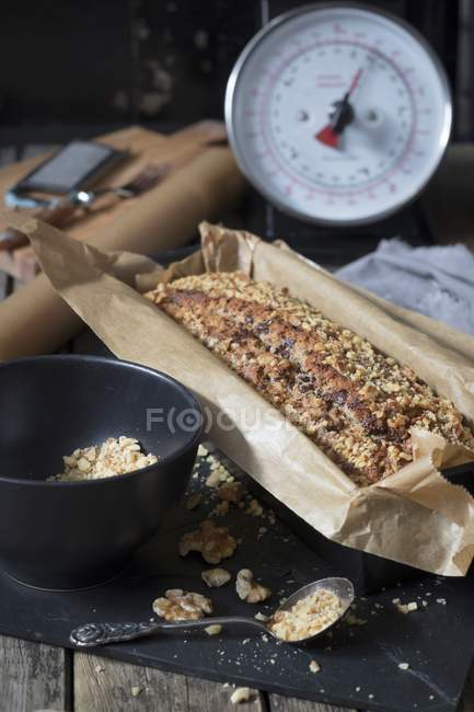 Banana bread with oat flakes and walnuts in baking dish and ingredients — Stock Photo