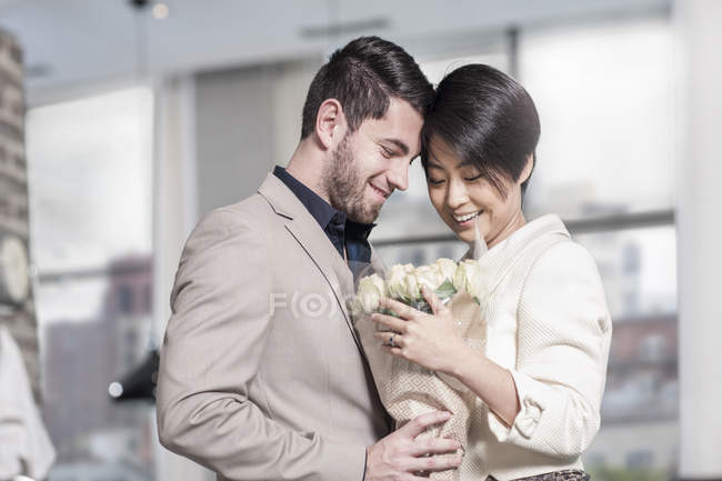 Man handing over roses to woman at home — Stock Photo