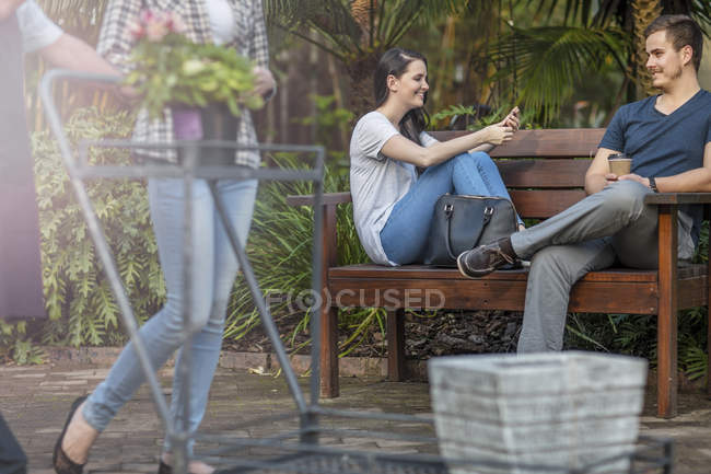 Пара, сидя на деревянной скамье сад центр — стоковое фото
