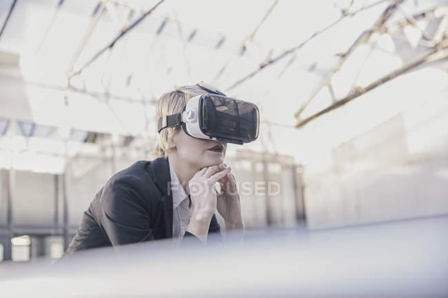 Empresária usando óculos de realidade virtual — Fotografia de Stock