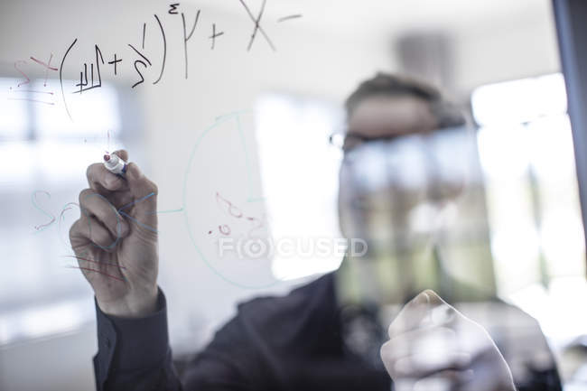Businessman writing on glass screen — Stock Photo