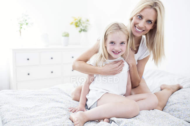 Портрет посміхаючись мати всеосяжне дочку на ліжку — стокове фото