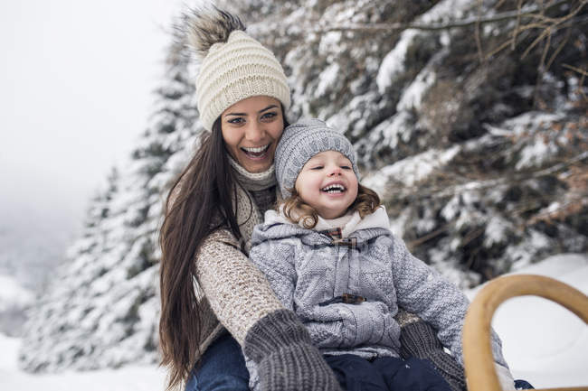 Happy mother with daughter on sledge in winter landscape — Stock Photo