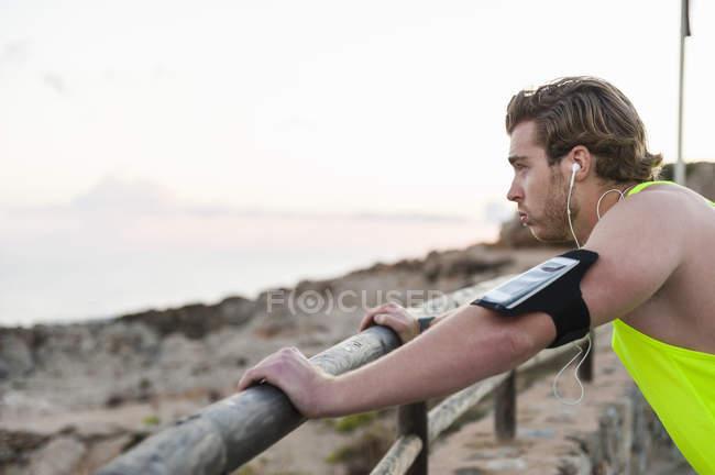 Jogger de pé na praia e ouvir música — Fotografia de Stock