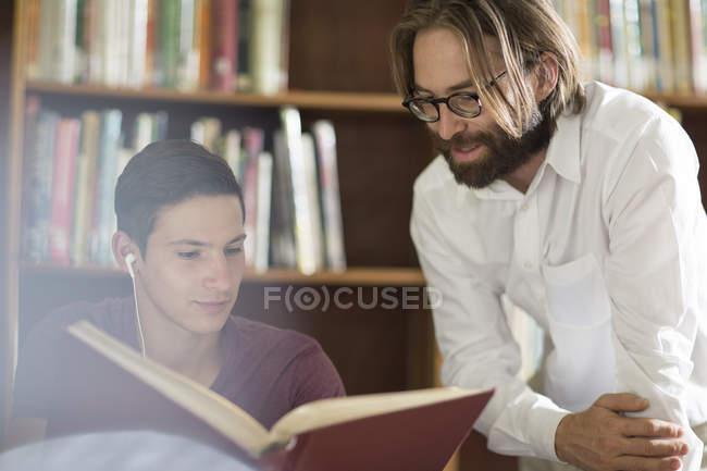 Studente di scuola superiore in libreria con il bibliotecario — Foto stock