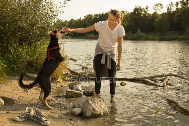 Young woman playing with her dog at riverside — Stock Photo