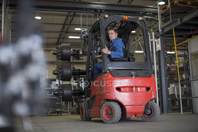 Factory worker driving forklift in warehouse — Stock Photo