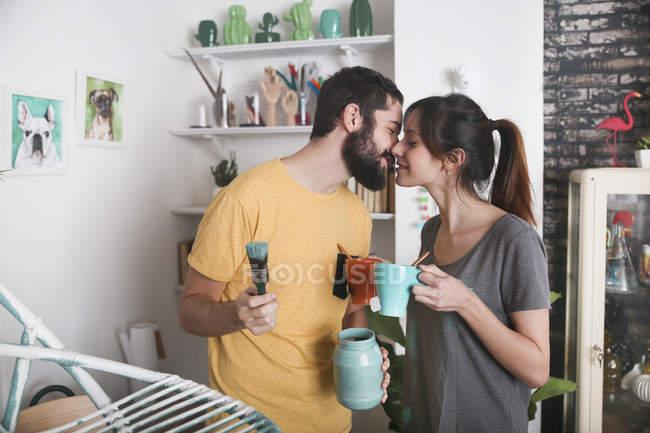 Junge Paar küssen zwischen Pinsel und Tee Tassen — Stockfoto
