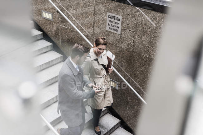 Businessman and woman walking downstairs in city — Stock Photo