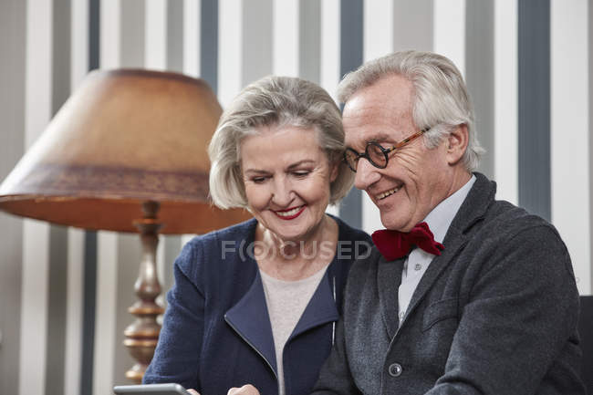 Happy senior couple using smartphone at home — Stock Photo