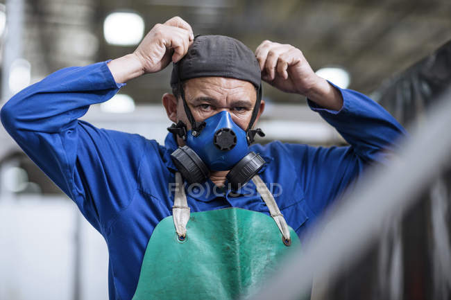 Worker putting on respirator in factory — Stock Photo
