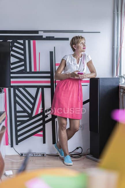 Femme écoutant de la musique sur smartphone dans un bureau moderne — Photo de stock