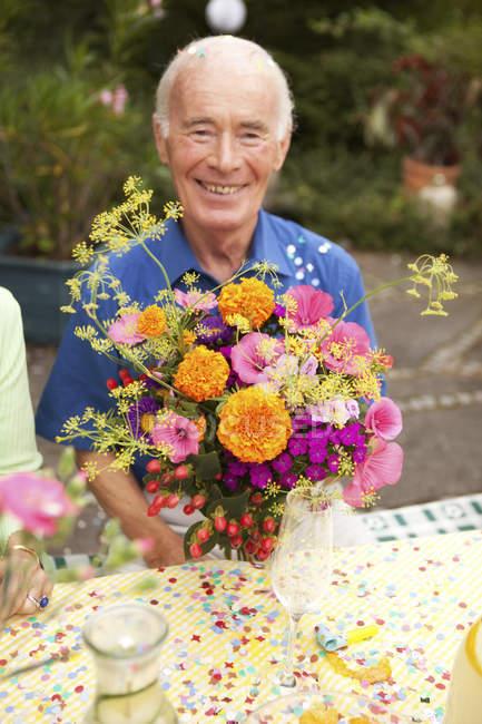 Seniorchef sitzt mit Blumenstrauß am Tisch — Stockfoto