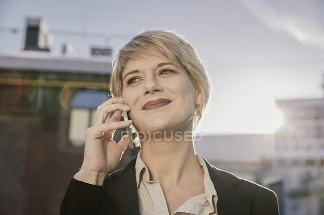 Portrait of smiling blond businesswoman on the phone at backlight — Stock Photo