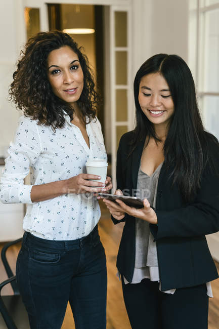 Two businesswomen drinking coffee and using digital tablet — Stock Photo
