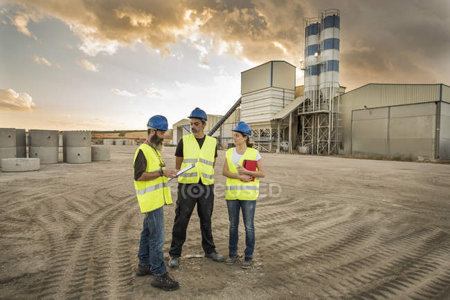 Three people in safety vests on industrial site — Stock Photo