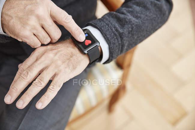 Senior überprüft medizinische Daten auf Smartwatch — Stockfoto