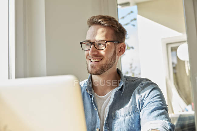Portrait of smiling man with laptop at home looking through window — Stock Photo