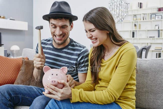 Porträt des Paares sitzen auf Sofa und brechen Sparschwein — Stockfoto