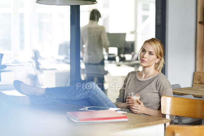 У женщины перерыв на кофе в офисе — стоковое фото