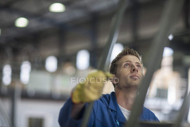 Factory worker standing on a ladder and looking up — Stock Photo
