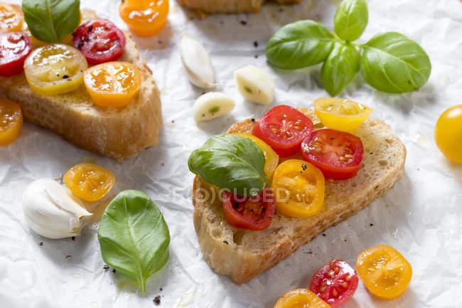 Крупным планом зрения ломтики хлеба с помидорами, чесноком и базиликом листья — стоковое фото